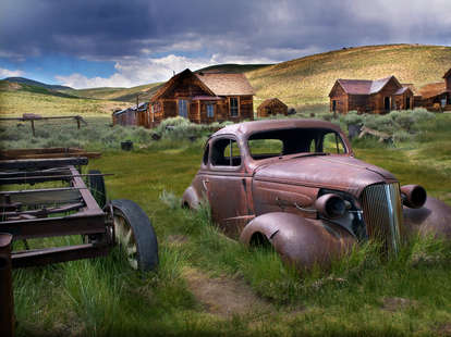 an old rusty car in the middle of a rural ghost town