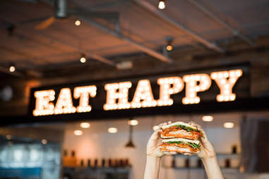 "Mendocino Farms sandwich in front of ""Eat Happy"" sign"