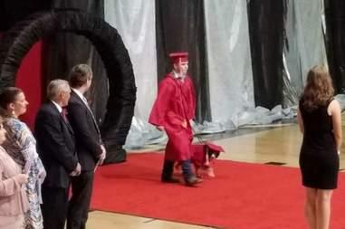 Kid graduates with service dog