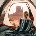 blanket-wrapped woman in a tent staring out at the desert