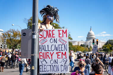 """Protester holding up sign saying """"Scare Em on Halloween. Bury Em on Election Day."""""""