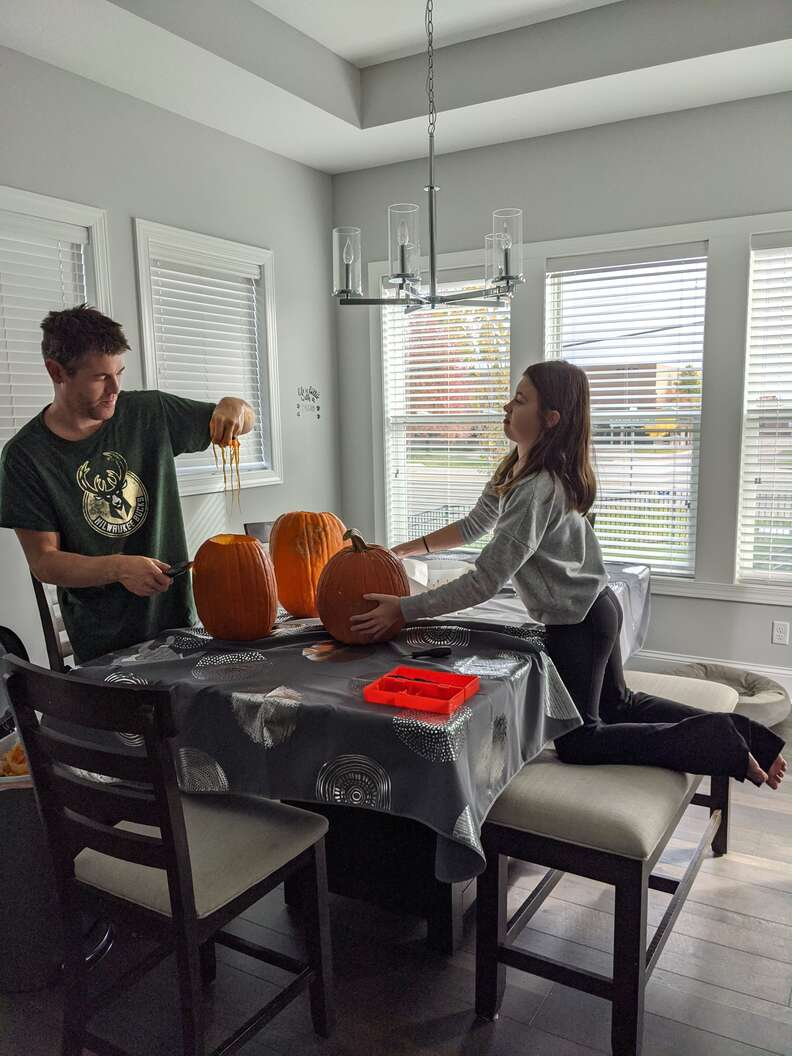 guy and daughter carve pumpkins to look like dog