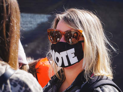 """A woman wears a mask that says """"VOTE"""""""