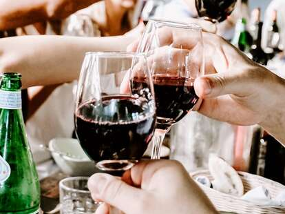 People holding glass of red wine.