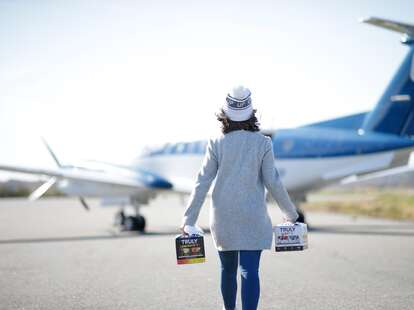 A person carrying cases of Truly Hard Seltzer approaches an aircraft.