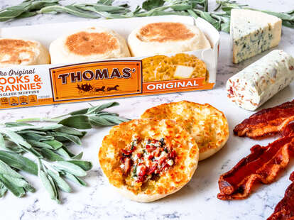 A toasted English muffin beside bacon and fancy cheese.