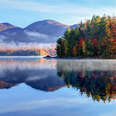 a forest of fall trees on the shores of a lake with foggy mountains in the distance