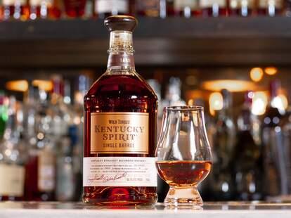 A bottle and a glass of Wild Turkey Kentucky Spirit on a bar.