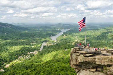 people on a cliff beneath an American flag overlooking sweeping forests and a river