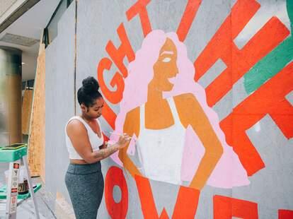 Tenbeete Solomon, aka Trap Bob, paints a mural outside of &pizza.