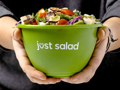 A person holds a Just Salad reusable bowl.