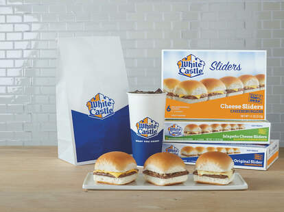 A White Castle takeaway bag, soda cup, and sliders on a plate.