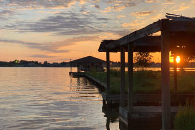 12 May 2019 Texas lake Conroe colorful sunset on lake with empty boathouse and green grass