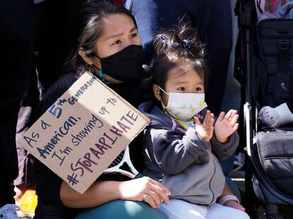 A mother and daughter listens to speakers at an AAPI rally to condemn Portsmouth Square in San Francisco's Chinatown in San Francisco, California