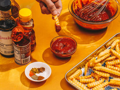 Hand dipping fry in ketchup