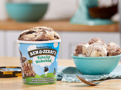 A pint of Ben & Jerry's Totally Unbaked beside a bowl of ice cream and a spoon.