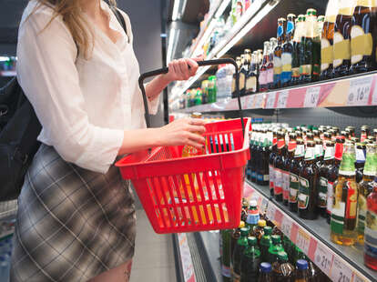 Woman buying beer at a grocery store