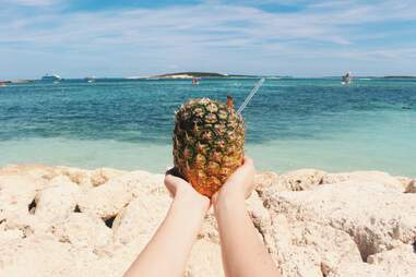 person holding pineapple on the beach