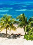 person on a hammock on a tropical beach