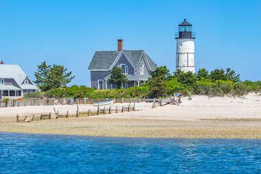 Sandy Neck Lighthouse dotting the blue coast of Cape Cod Bay along a sandy beach.
