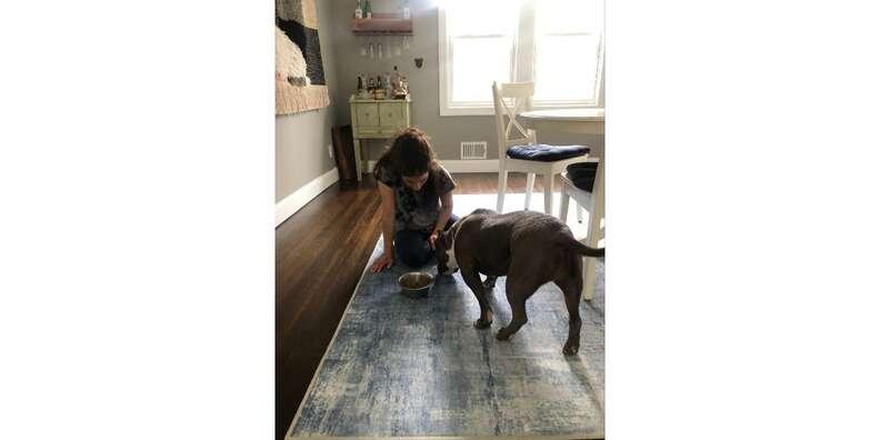 woman feeding dog on a Ruggable rug on floor