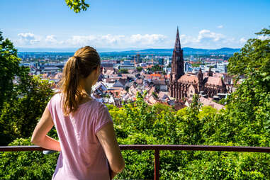 woman overlooking muenster cathedral in freiburg, germany