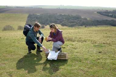 couple at the top of a hill looking through a geocache's contents