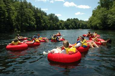 people in inner tubes floating down a tree lined river