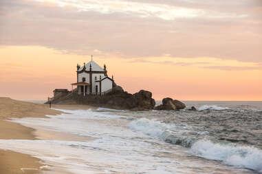 Capela do Senhor da Pedra chapel at sunset on Praia de Miramar, Portugal