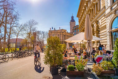 person riding bike past cafe in leipzig, germany