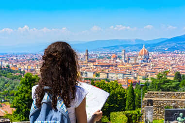 brunette Woman traveler with Map over Cathedral of Santa Maria del Fiore (Duomo) in Florence, Italy