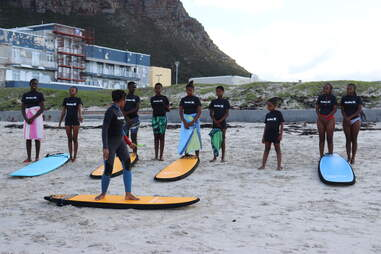 a group of young black girls practicing surfing