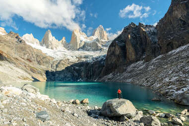 Man with hiking poles and red t-shirt standing on a rock admiring Laguna Sucia and Fitz Roy range from above in autumn