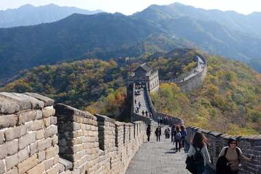 people walking along a mountainous section of the Great Wall of China