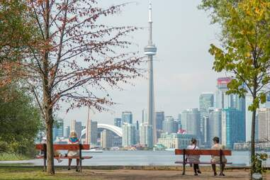 people sitting on benches with view of city and Toronto tower