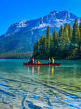people canoeing on a crystal clear lake in front of mountains and a giant forest