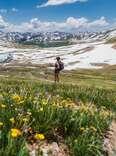 woman hiking through wildflowers in a mountain range