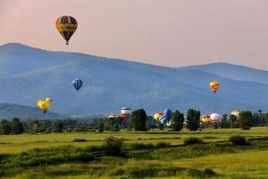 hot air balloons taking flight in the mountains