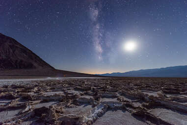 Milky way and the moon over flat, rocky salt flats