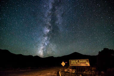Information Sign On Road By Silhouette Mountains Against Star Field