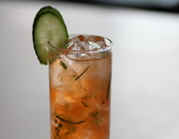 A cocktail garnished with a cucumber