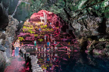 people crowded near an underground cavernous lake