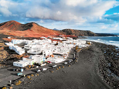 a white-painted village in the mountains on a black sand beach