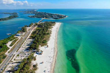 Aerial view of Coquina Beach with white sand beach, trees, and the main road