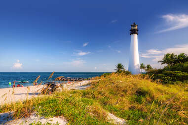 people sitting with umbrellas on the beach beneath the Cape Florida Lighthouse