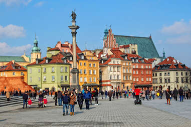 People walk in Castle Square in Warsaw in Old Town with the Column of King Zygmunt III Waza & ancient houses in the background