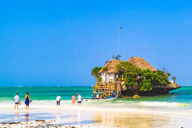 people waiting for boat to famous restaurant on a rock in Zanzibar