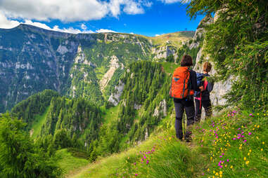 people hiking along a mountain cliff near a valley filled with wildflowers