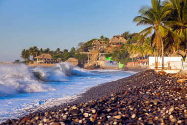 waves crashing against a rocky shore near a tropical village