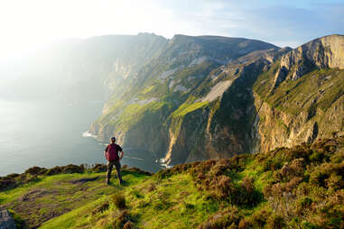 person standing looking out at the ocean from enormous cliffs